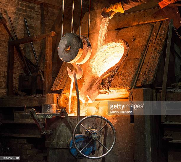 Worker adding flux to molten metal in foundry