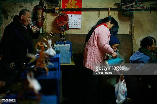 Worker adds boiled water for customers at a Laohuzao teahouse at an alleyway January 23, 2007 in Shanghai, China. Laohuzao is a traditional store...