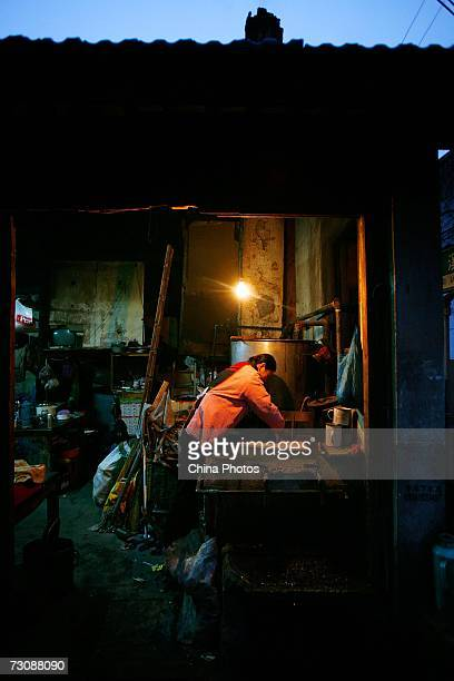 Worker adds fuel to the stove at a Laohuzao teahouse at an alleyway January 23, 2007 in Shanghai, China. Laohuzao is a traditional store which sells...