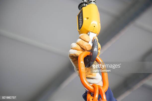 worker adjusting chain hoist in industrial plant - sigrid gombert stock-fotos und bilder