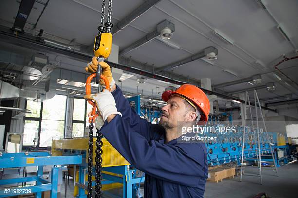 worker adjusting chain hoist in industrial plant - sigrid gombert stock pictures, royalty-free photos & images