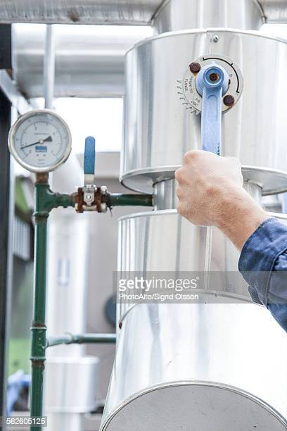 worker adjusting control lever on industrial equipment - incinerator stock photos and pictures