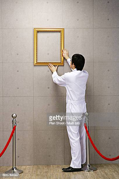 Worker adjusting empty picture frame on concrete wall