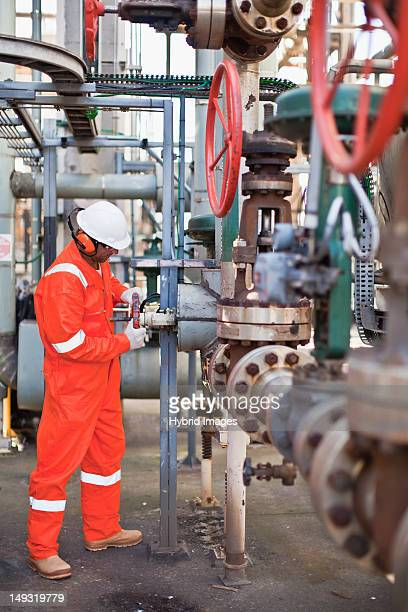 worker adjusting gauge at oil refinery - air valve stock photos and pictures