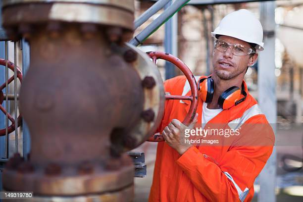Worker adjusting gauge at oil refinery