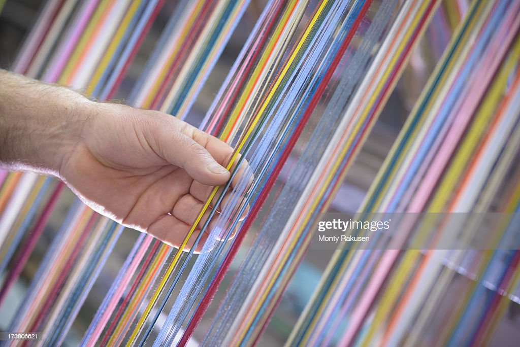 Worker adjusting multicoloured silk yarn on industrial loom in textile mill : Stock Photo