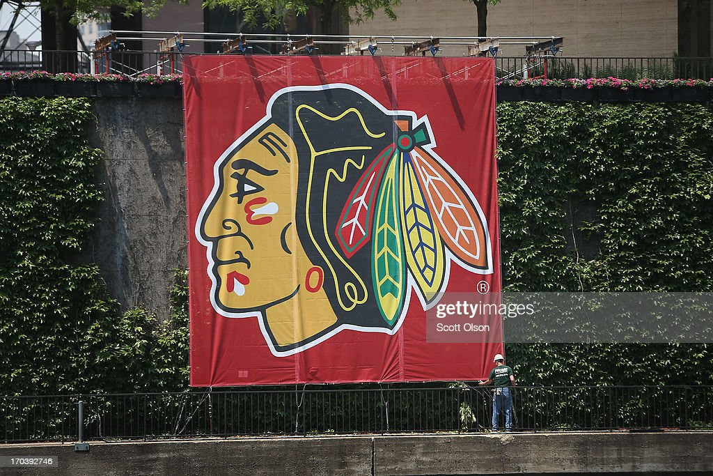 A worker adjusts a Chicago Blackhawks' banner alongside the Chicago River in the Loop on June 12, 2013 in Chicago, Illinois. The Chicago Blackhawks will match up against the Boston Bruins tonight at the United Center in the first game on the NHL Stanley Cup playoffs.