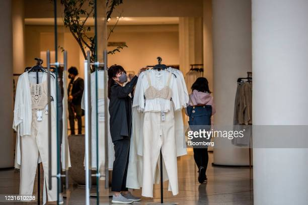 Worker adjusts a clothing display by the entrance to a Zara clothing store, operated by Inditex SA, in Barcelona, Spain, on Monday, March 8, 2021....