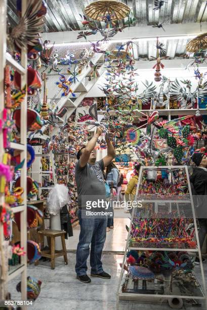 A worker adjusts Alebrijes Mexican folk art sculptures displayed for sale at the Ciudadela Market in Mexico City Mexico on Tuesday Oct 17 2017 The...