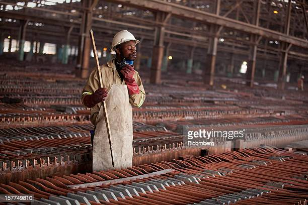 A worker adjusts his breathing mask as he handles copper sheets during electrolytic refining in the metallurgical plant at Katanga Mining Ltd's...