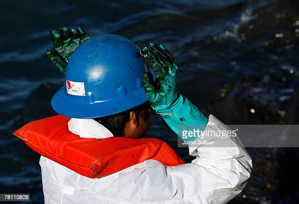 A worker adjusts his helmet with oil covered gloves as he cleans oil from rocks along the Berkeley Marina November 27 2007 in Berkeley California...