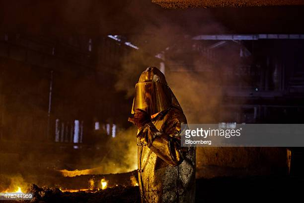 Worker adjusts his safety visor as he operates in the blast furnace in at ArcelorMittal's steel plant in Ostrava, Czech Republic, on Monday, Aug. 26,...