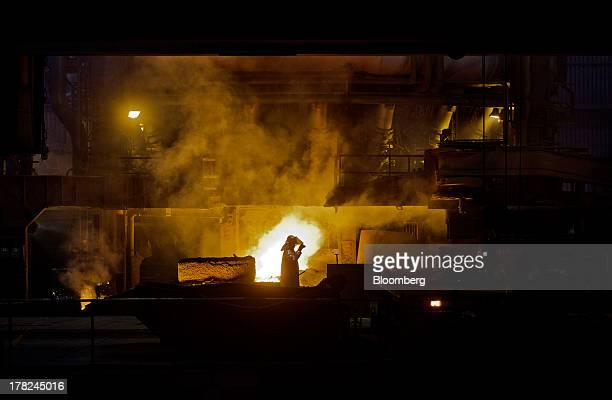 Worker adjusts his safety visor as he works near the blast furnace at ArcelorMittal's steel plant in Ostrava, Czech Republic, on Monday, Aug. 26,...