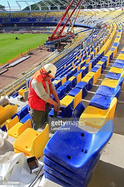 A worker adjusts new seats at Estadio Municipal de Concepción Alcaldesa Ester Roa Rebolledo is seen during restoration prior to Copa America Chile...