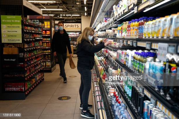 Worker adjusts products on a shelf at the Amazon.com Inc. Amazon Fresh cashierless convenience store in the Ealing area of London, U.K., on Thursday,...