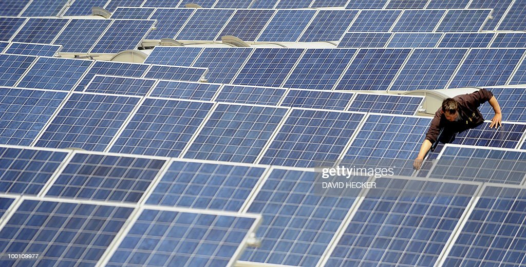 A worker adjusts solar panels on the roof of a building in the northern German city of Bremen on May 21, 2010. The 50000 square metre construction is expected to produce 1 megawatt of electricity per year.