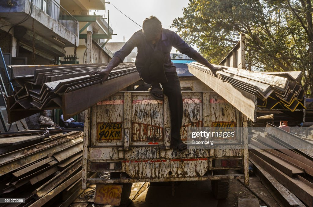 A worker alights from the back of a truck carrying iron