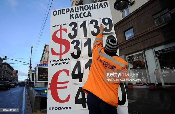 A worker an exchange office replaces numbers on a board listing foreign currency rates against the Russian ruble in central Moscow on November 29...