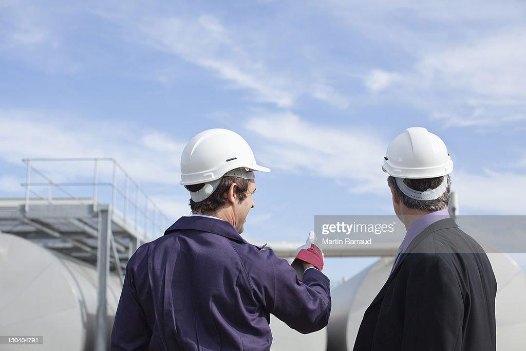 Trabajador y empresario examinando tanques al aire libre : Foto de stock