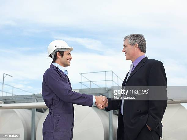 Worker and businessman shaking hands outdoors