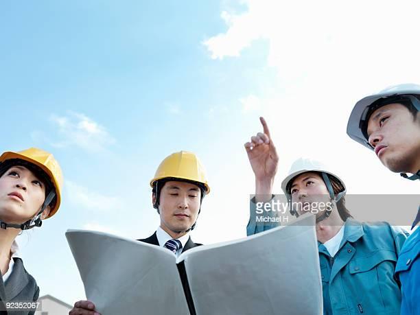 Worker and businessman who talks around blueprint