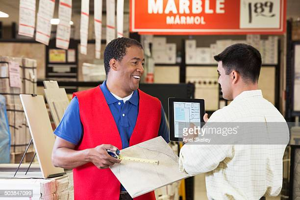 Worker and contractor discussing plans in home improvement store
