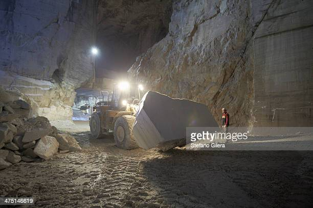 Worker and excavator in marble quarry