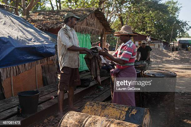 A worker and his supervisor wipe their hands clean of oil at the recycling factory on the banks of the Irrawaddy River on December 16 2013 in Yangon...