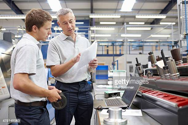 Worker and manager meeting in engineering warehouse