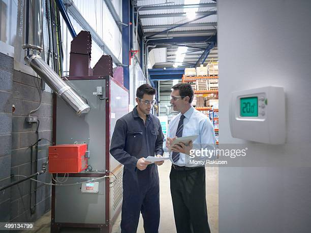 Worker and office manager discuss energy use next to boiler in factory