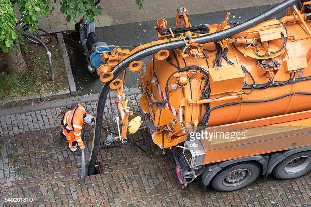 worker and sewage truck, high-angle view - sewer stock pictures, royalty-free photos & images