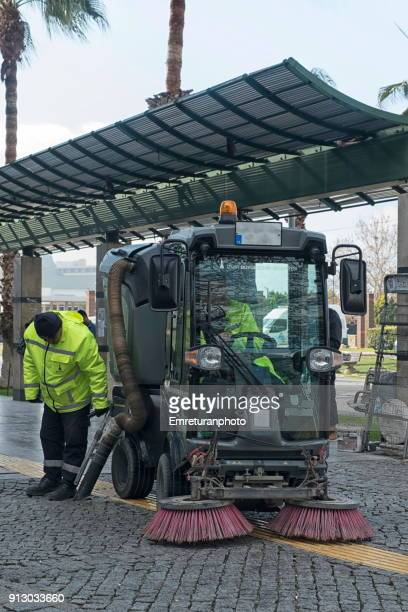worker and sweeper cleaning streets. - emreturanphoto stock pictures, royalty-free photos & images