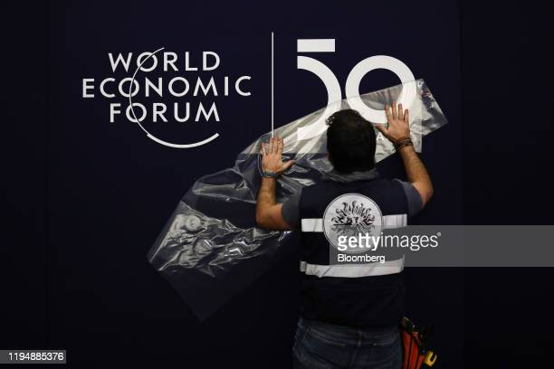 A worker applies a transfer on the wall inside the Congress Center ahead of the World Economic Forum in Davos Switzerland on Monday Jan 20 2020 World...