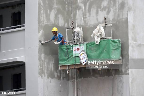 A worker applies cement plastering on a newly constructed public housing building in Singapore on December 9 2017 / AFP PHOTO / ROSLAN RAHMAN