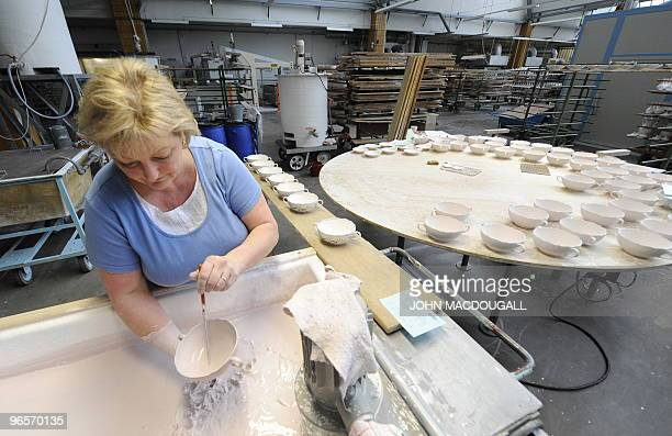 A worker applies glaze on porcelain items at the Meissen porcelain manufacture in Meissen January 20 2010 The Meissen porcelain manufacture a...