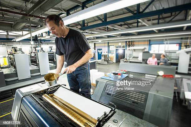 Worker applying gold ink to printing machine in print workshop