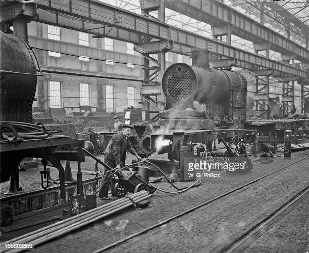 A worker applying local heat to the bent frame of a steam locomotive at the London Midland and Scottish Railway works at Crewe Cheshire 12th March...
