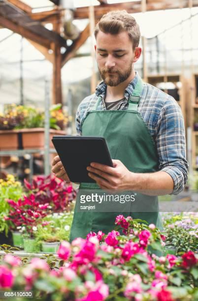 Worker ar the Garden Center Looking at Digital Tablet