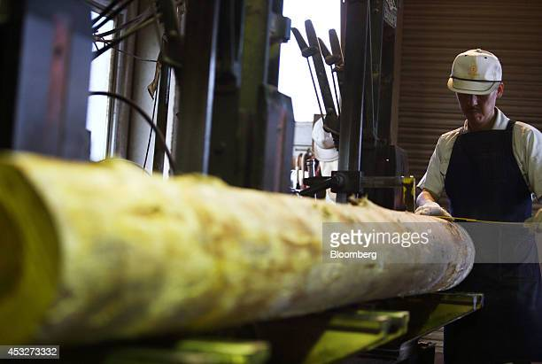 A worker arranges a log to be processed at the Okikura Lumber Mill facility in Akiruno City Tokyo Japan on Friday Aug 1 2014 Along with farming the...