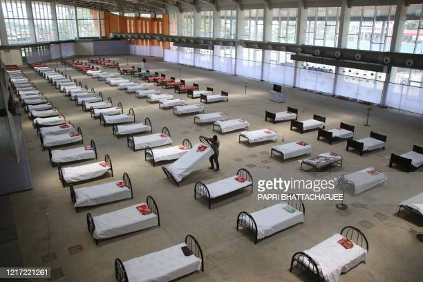 TOPSHOT A worker arranges beds at quarantine centre set up in the Hapania International Fair Complex during a nationwide lockdown imposed as a...