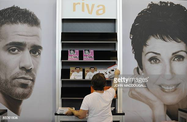 A worker arranges books at a stand displaying portraits of German rapper Bushido and German author Erika Berger of the Frankfurt Book Fair October 14...