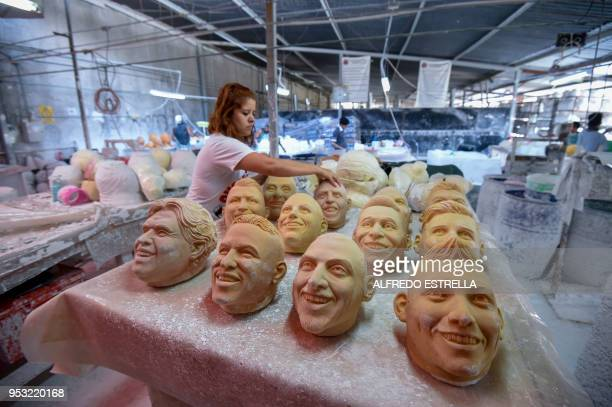 A worker arranges latex masks of football players at a factory in Jiutepec Morelos State Mexico on April 20 2018 / TO GO WITH AFP STORY by JEAN LUIS...