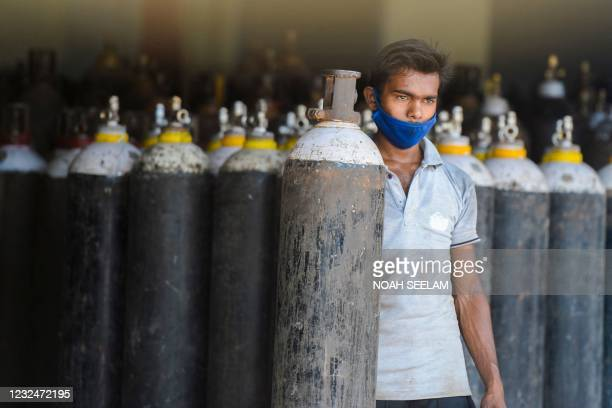 Worker arranges medical oxygen cylinders to transport to hospitals for the Covid-19 coronavirus treatment in a facility on the outskirts of Hyderabad...