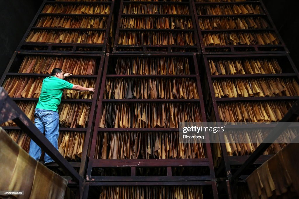A worker arranges rubber sheets on racks for drying in the smoke house at the Thai Hua Rubber Pcl factory in Samnuktong, Rayong province, Thailand, on Wednesday, Jan. 29, 2014. Rubber production in Thailand, the world's largest exporter, may decline as growers from the main producing regions join protests seeking to overthrow the government, according to Von Bundit Co. Photographer: Dario Pignatelli/Bloomberg via Getty Images
