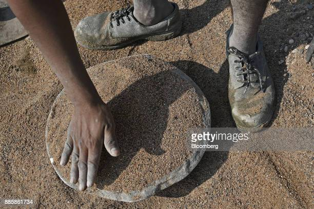 A worker arranges sand in a container at an under construction sewerage system on the project site for a 920squarekilometer industrial area located...