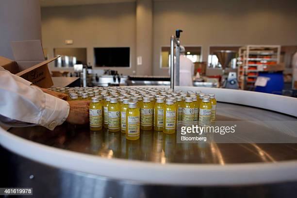 A worker arranges small bottles of shower wash bodycare products during manufacture at the Fresh Line Cosmetics production plant in Koropi Greece on...