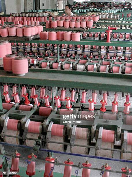 A worker arranges spools on the product line weaving Shu Brocade at a Shu Brocade factory on June 28 2005 in Chengdu of Sichuan Province China Shu...
