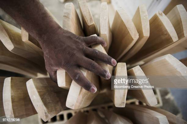 A worker arranges unfinished cricket bats at a factory