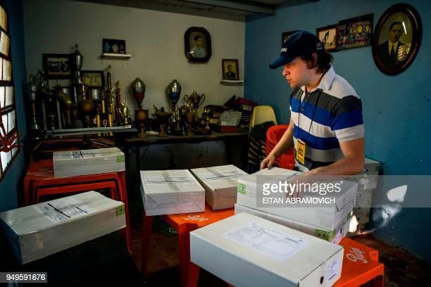 A worker arranges voting material at a polling station ahead of the upcoming April 22 presidential elections in Asuncion on April 21 2018 Opinion...