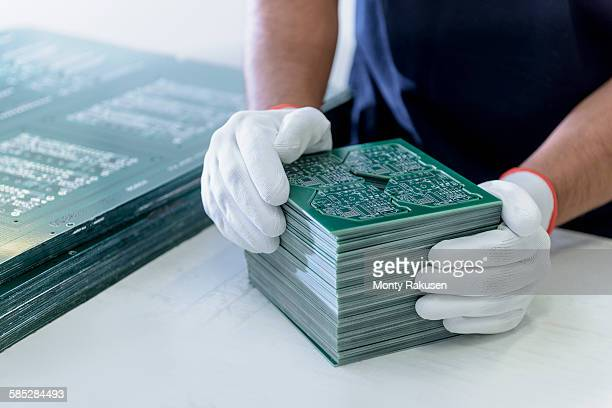 Worker arranging cut circuit boards in circuit board factory